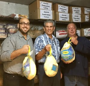 Two restaurant owners and Federation President hold up donated turkeys.