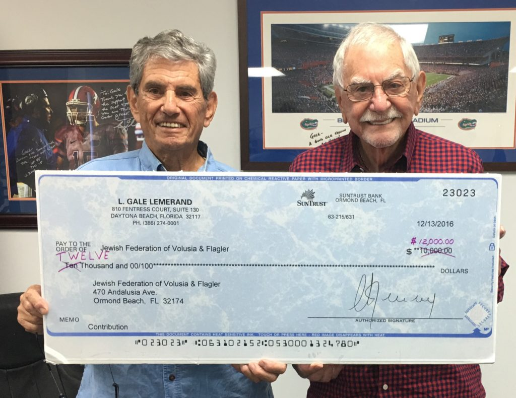Jewish Federation President Marvin Miller, left, and philanthropist Gale Lemerand hold last year's donation for $10,000 -- which Lemerand increased to a $12,000 matching grant this year.